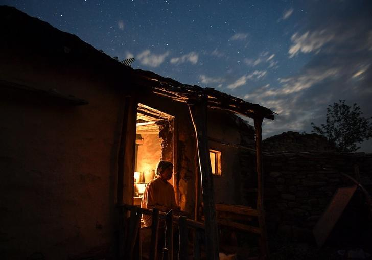 woman sitting in the doorway of her house at twilight