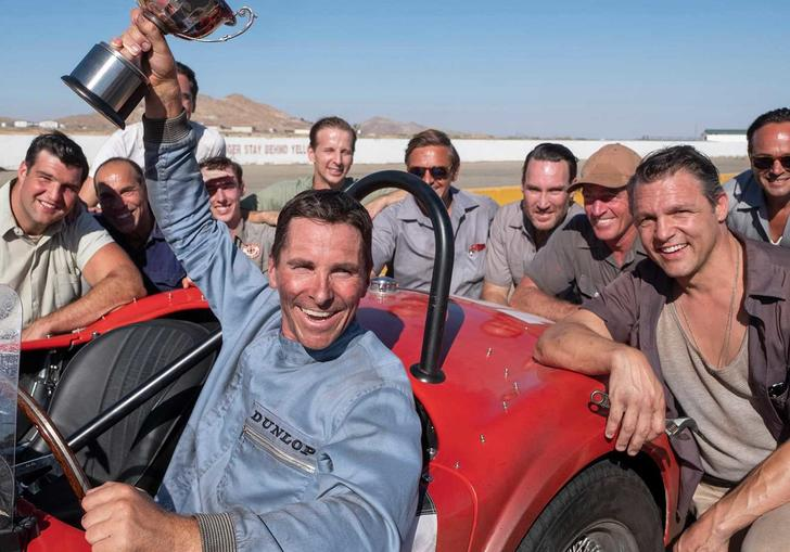 christian bale in Le Man 66 holding a trophy aloft sitting in a red car