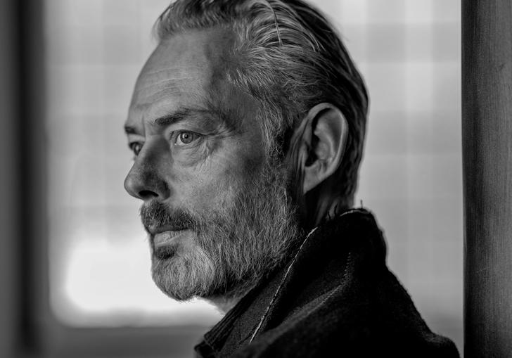 A black and white portrait of Mark Padmore gazing into the distance