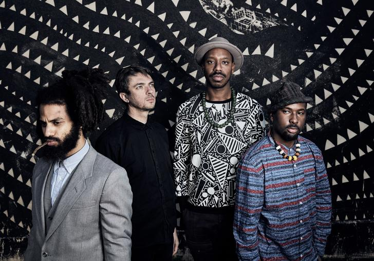 Sons of Kemet standing in front of a patterned wall