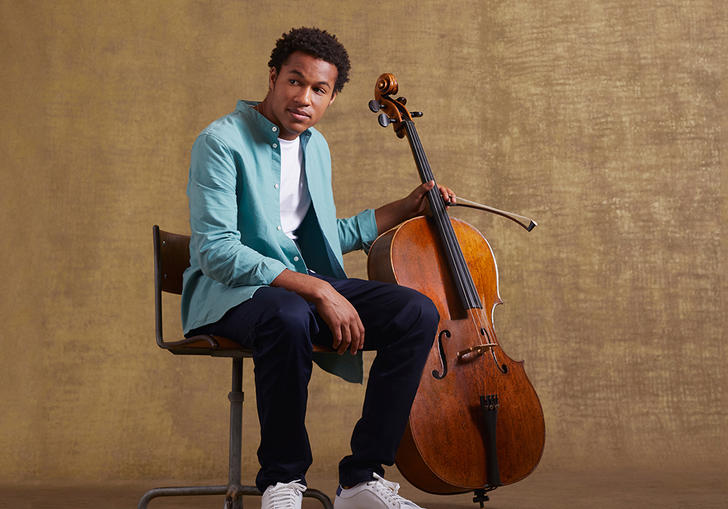 Sheku sitting on a chair holding his cello