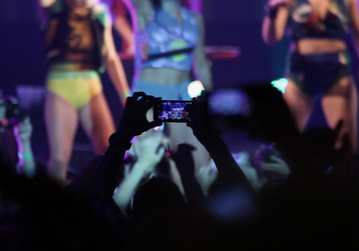 a person in a crowd holds their phone up to film the girl band on stage