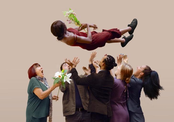 Five people launch a person into the air, as she holds a flower bouquet