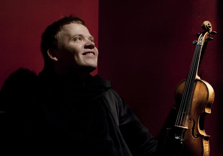 Pekka smiling joyfully as he gazes into the middle distance, violin in hand