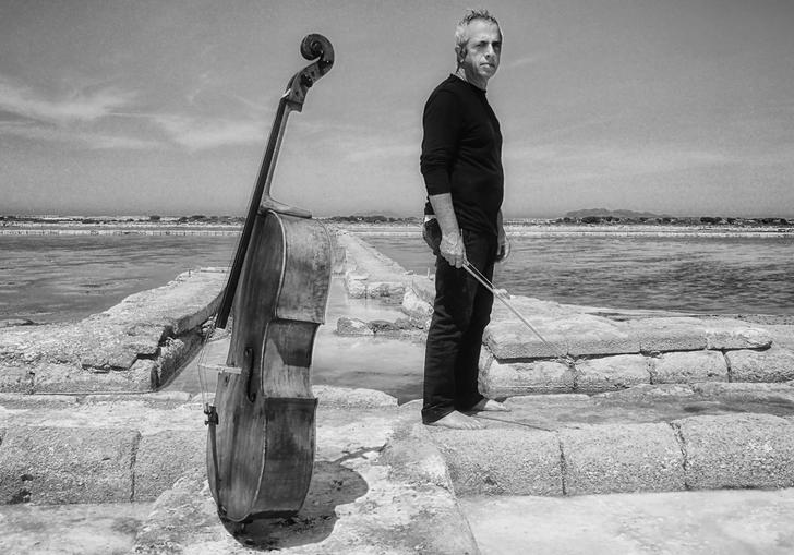 A black and white image of a pensive Giovanni standing barefoot on some ruins in a dry and barren wasteland, his cello standing upright close by
