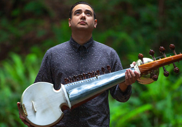 Alam Khan holding his Sarod instrument, surrounded by greenery, looking upwards