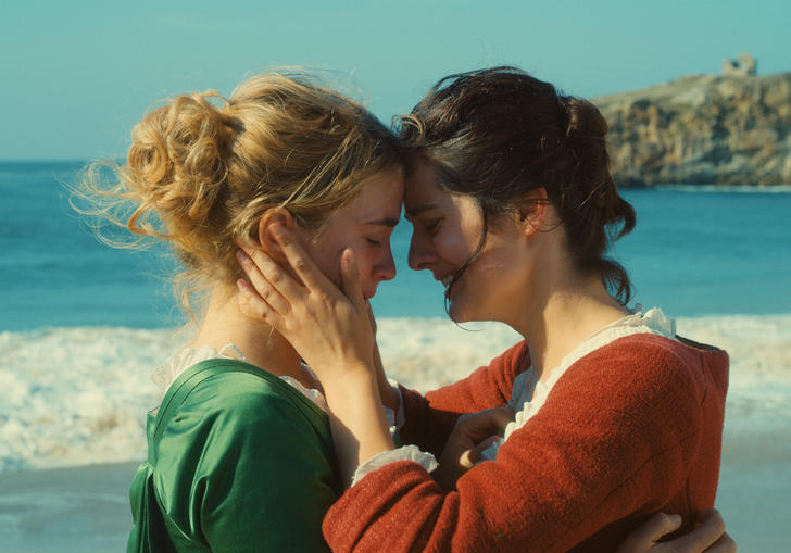 Two women embrace on a windswept beach