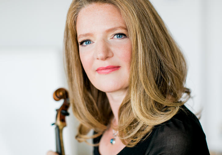 A portrait Rachel Podger, violin in hand, her blue eyes glistening