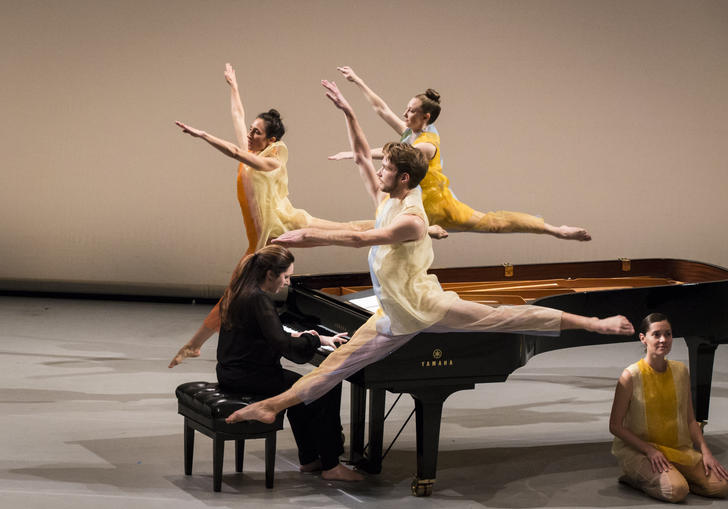 three dancers in yellow leap around a grand piano, one dancer is sat on the floor