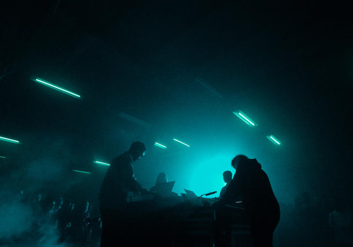 A live performance featuring four musicians facing each other with smoke and stobe lights around them