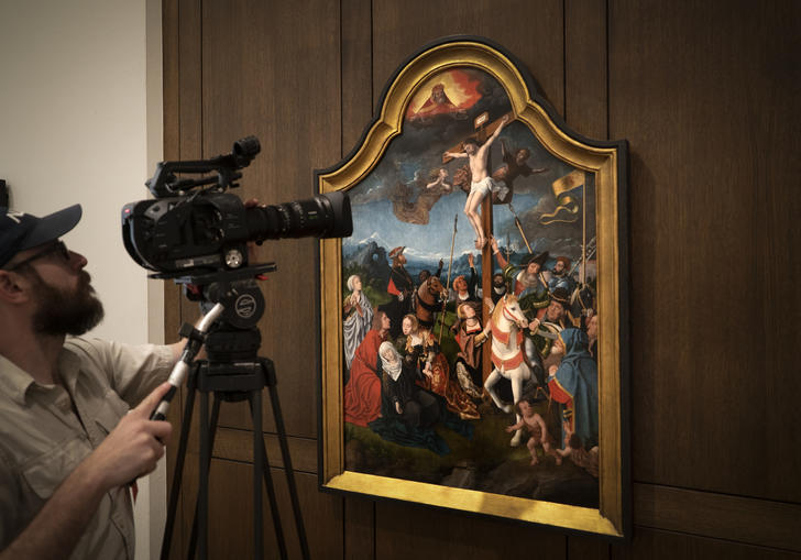 A man films a painting depicting the crucifixion of Jesus Christ