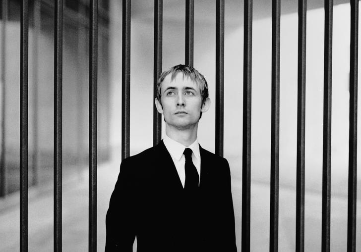 black and white photo of Neil Hannon wearing a suit against a backdrop of vertical bars