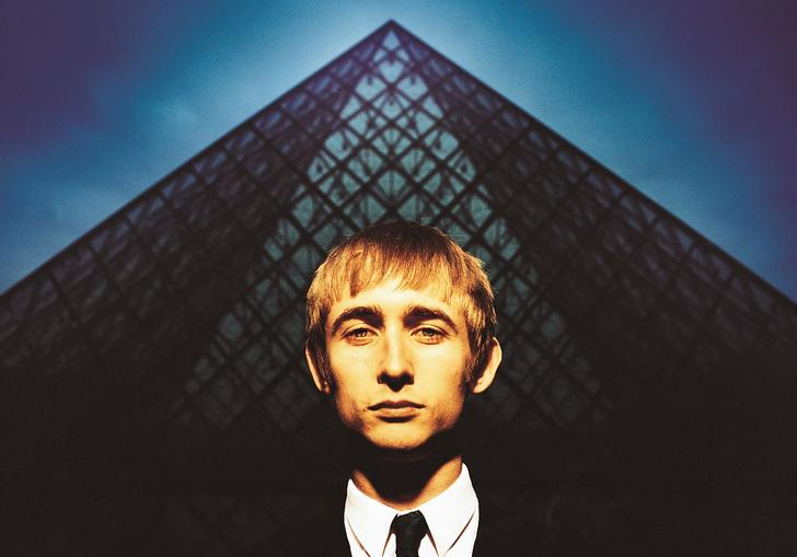 Neil Hannon in a black and white suit and tie standing in front of a blue pyramid