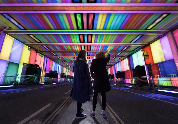 People in a colourful tunnel
