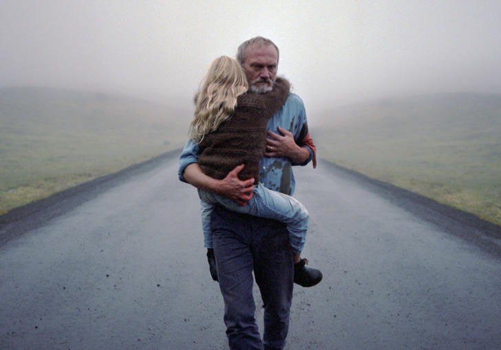A man carrying a young girl along a deserted road