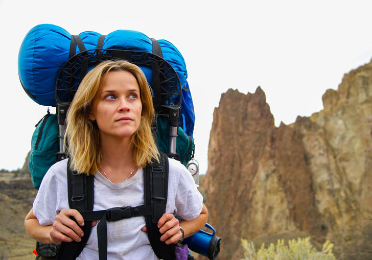 reese witherspoon with hiking bags in the middle of some mountains