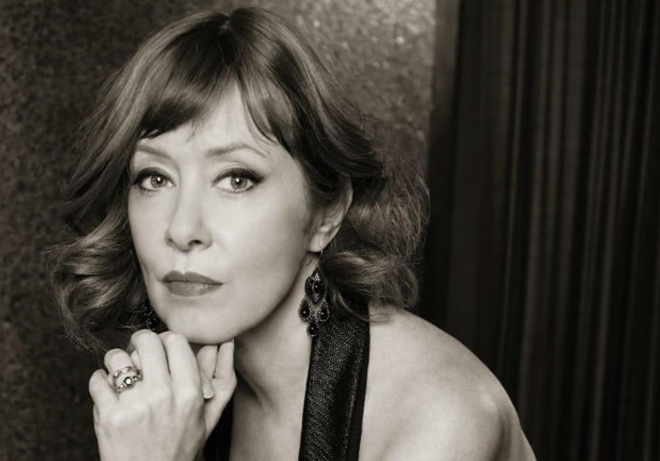 black and white photo of suzanne vega. resting her chin on her hand.