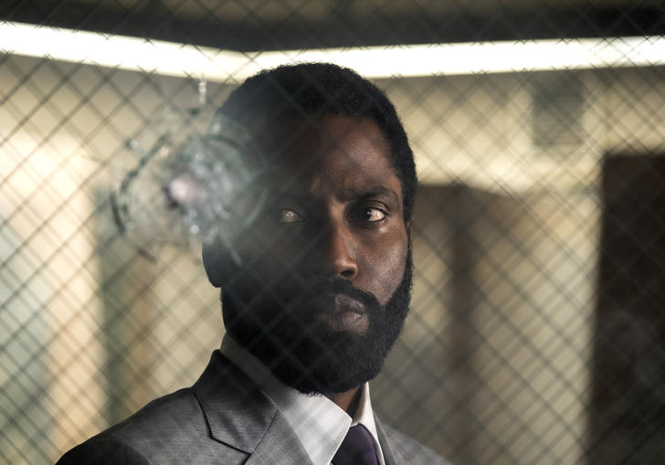 A close up of John David Washington behind glass with criss-cross wiring and a bullet hole