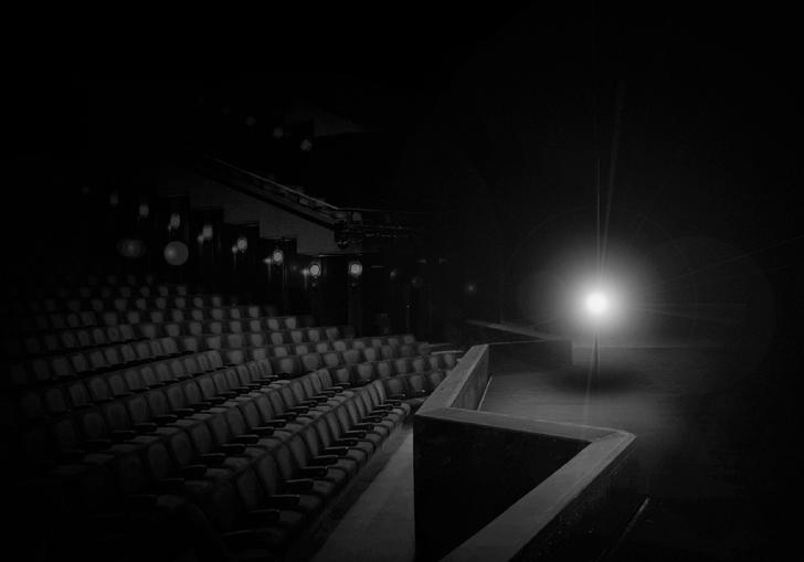 An empty Barbican Theatre lit with just a single white light on a stand stood on an empty stage.