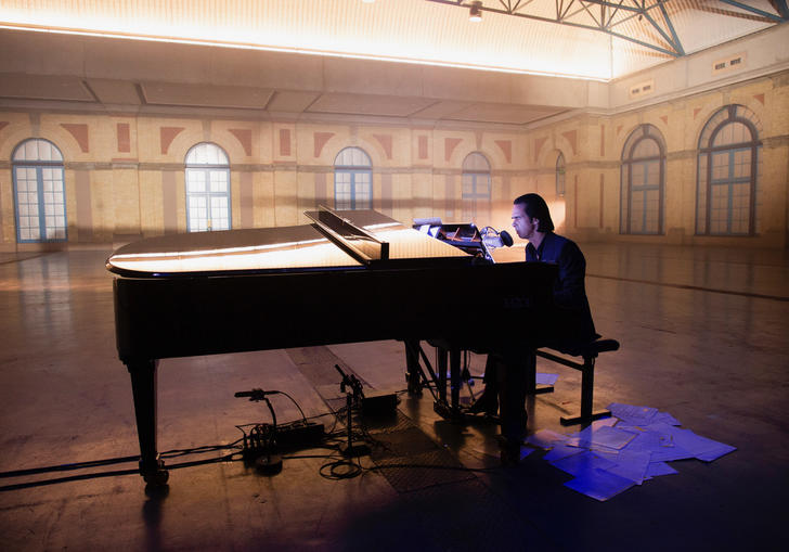 Nick Cave sitting at the piano in Alexandra Palace