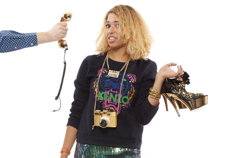 Paula Varjack holding stiletto shoes, looking at the camera unimpressed as someone holds up a phone with cut-off cord to her