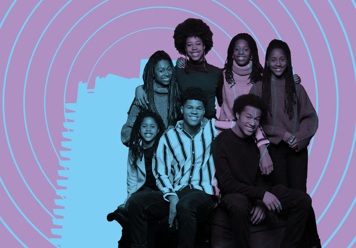 The Kanneh-Mason Family smiling with the Barbican tower illuminated on them