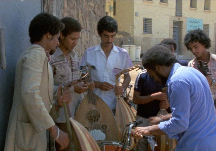 A group of men gather round some instruments on the street in bright sunlight