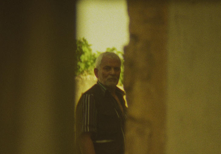 An older man looks through a gap in two walls