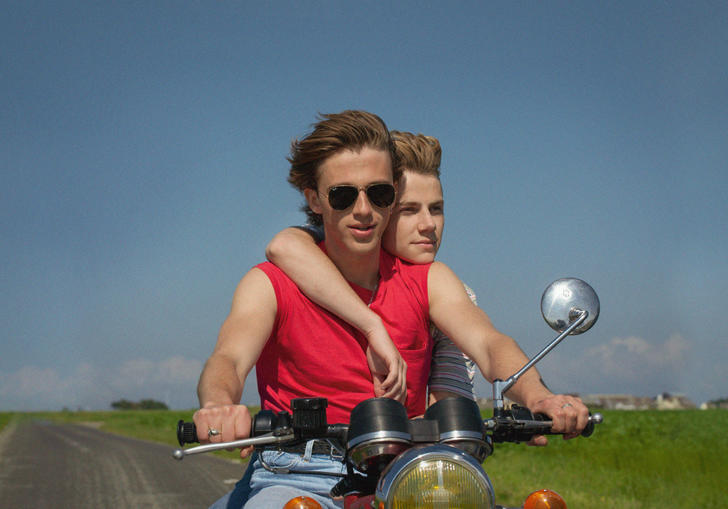 two boys on a motorbike with blue sky behind them
