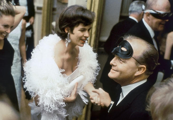 Capote sitting in a room with a mask on his head surrounded by people