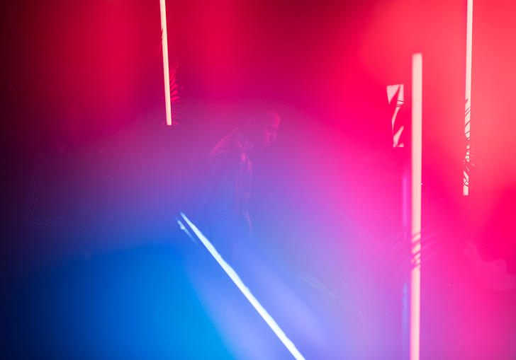 A faint outline of a young man in a neon pink and blue environment