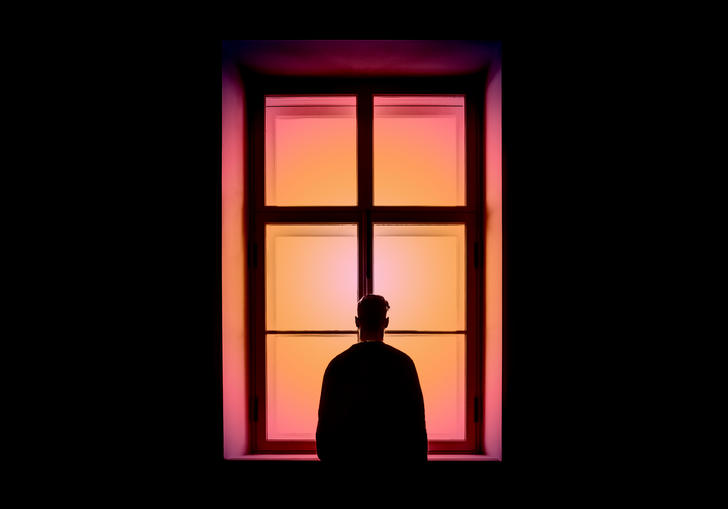 Silhouette of man looking out of a pink window