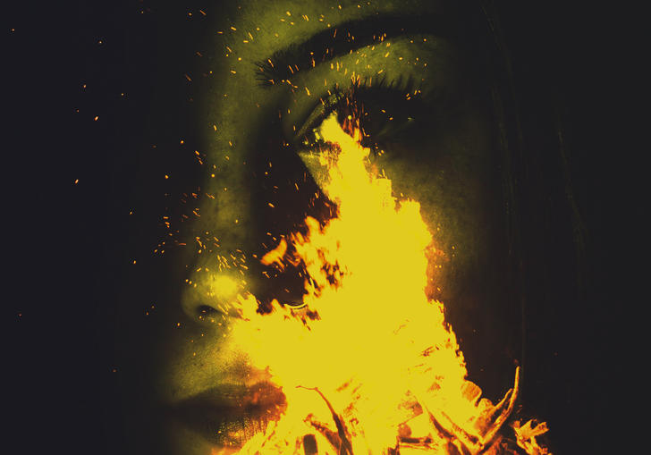 Image of woman's face behind campfire