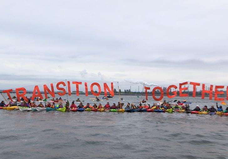 climate activists tie themselves together in kayaks holding a sign that says 'transition together'