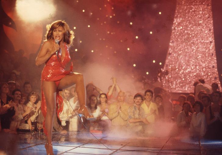 Tina Turner singing in a red outfit