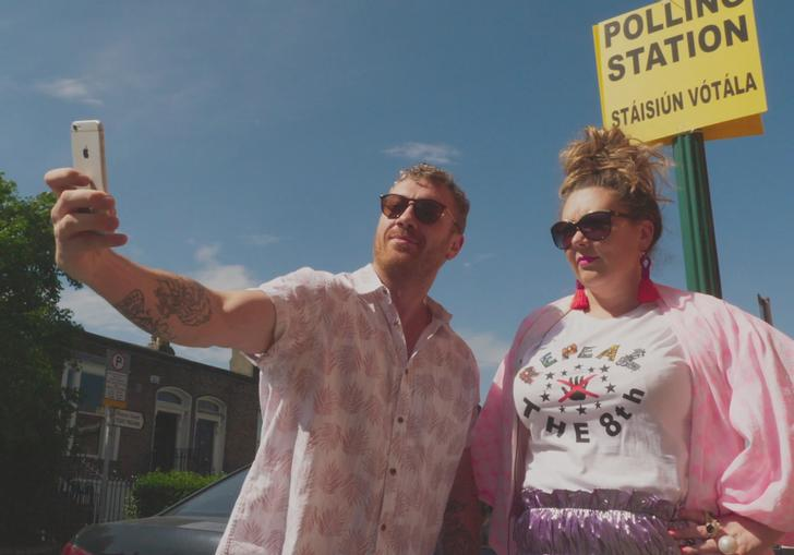 a man and a woman dressed in pink take a selfie with the polling station sign behind them