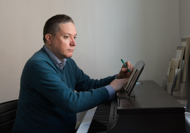 A picture of Julian Anderson writing at the piano