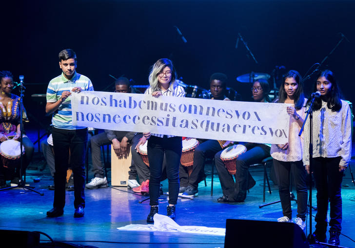students on stage holding a banner