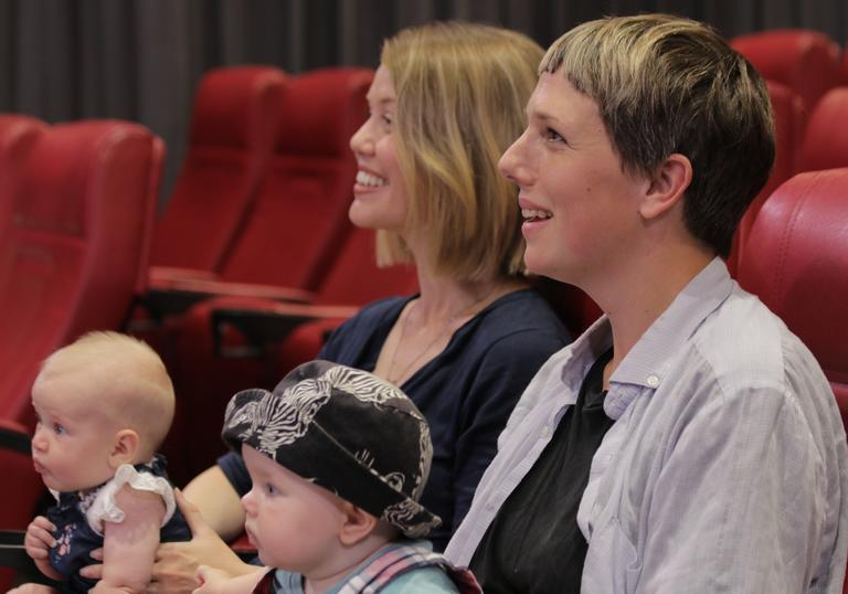 Photo of two women with babies watching a film in the Barbican cinema