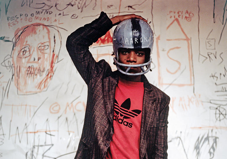 Photo of Basquiat wearing an Adidas tshirt, suit and football helmet