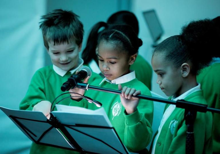 Photo of three young children by a microphone looking at sheet music