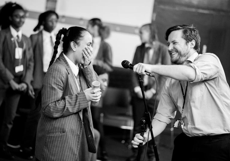 Photo of girl in school uniform laughing as teacher holds microphone