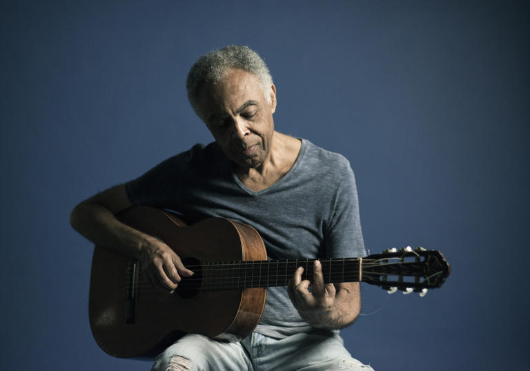 Gilberto Gil looking blue whilst playing his guitar in blue jeans and a blue t-shirt in front of a blue background