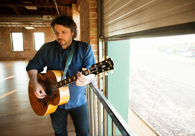 Jeff Tweedy playing guitar in the corner of a large room with exposed brick walls