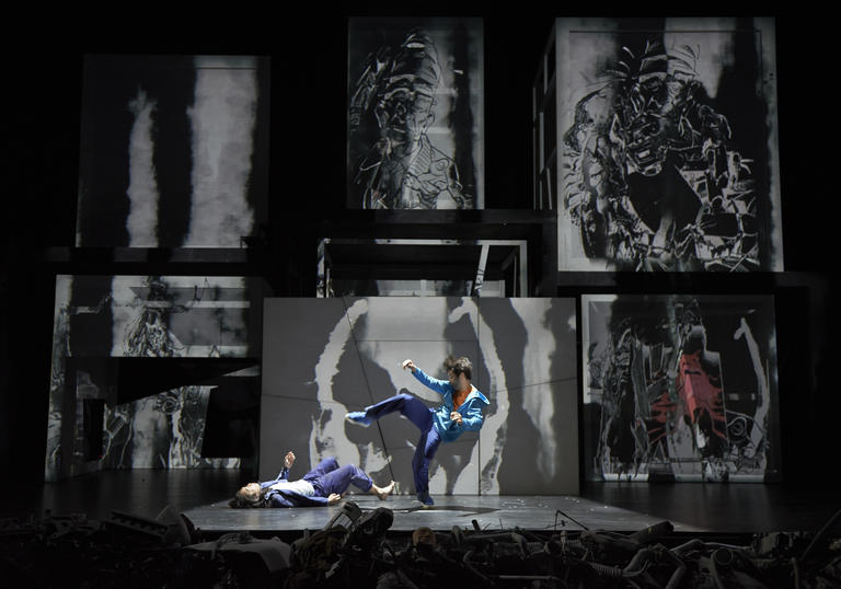 two dancers on stage against a backdrop of black and white paintings
