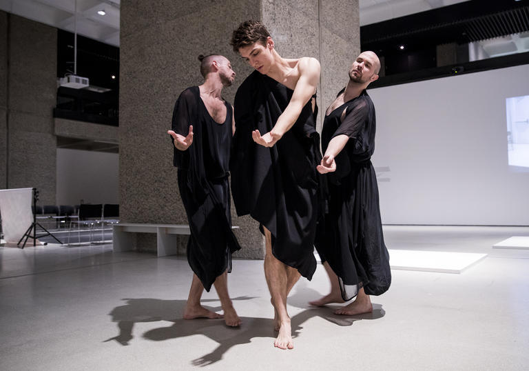 Photo of three men in robes dancing in Trajal Harrell