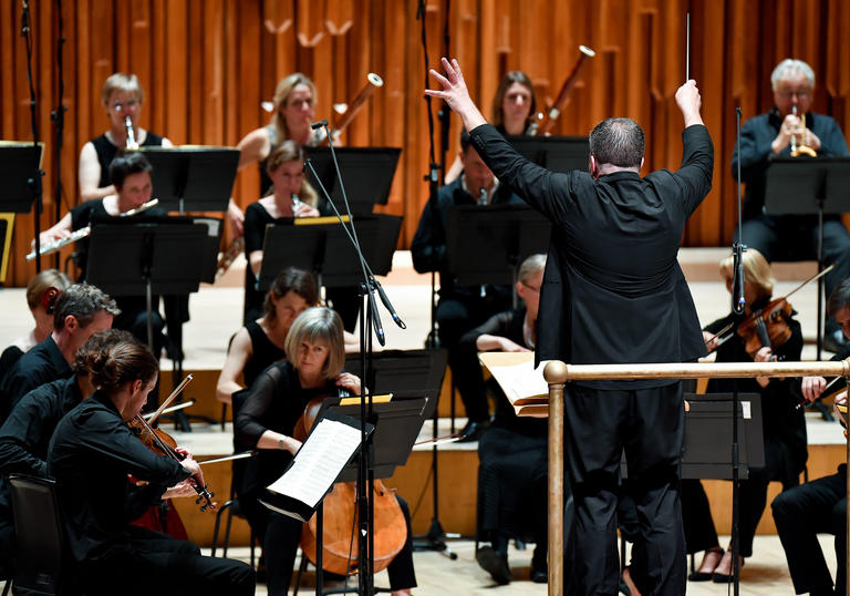 photo of britten sinfonia and man conducting an orchestra
