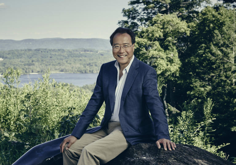 Yo Yo Ma sitting on a rock