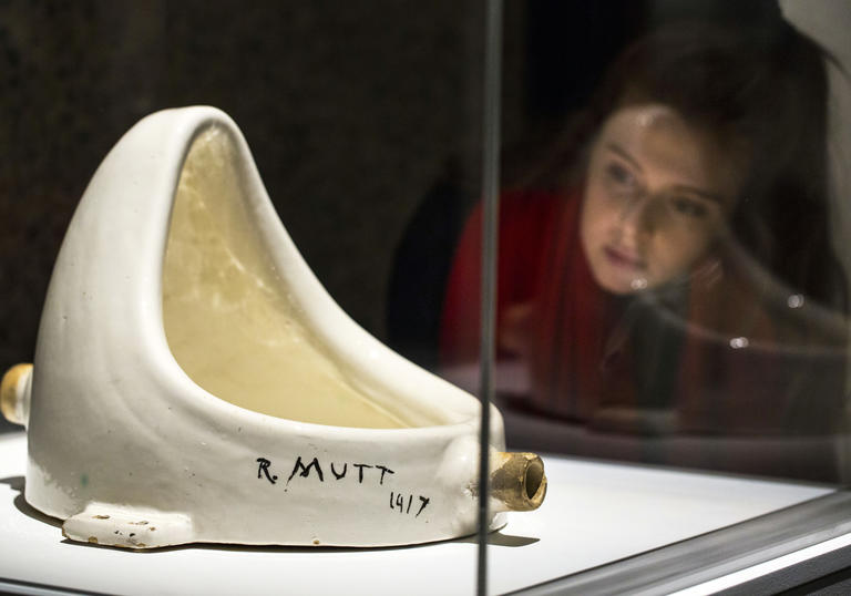 A woman looks at Duchamp's urinal sculpture, Fountain