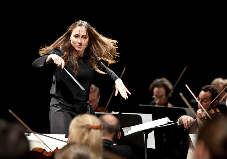 Joana Carneiro conducting on stage landscape